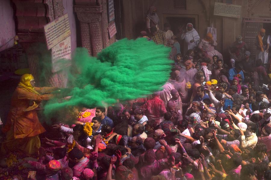 Участник праздника распыляет зеленый порошок на толпу людей в Индии.