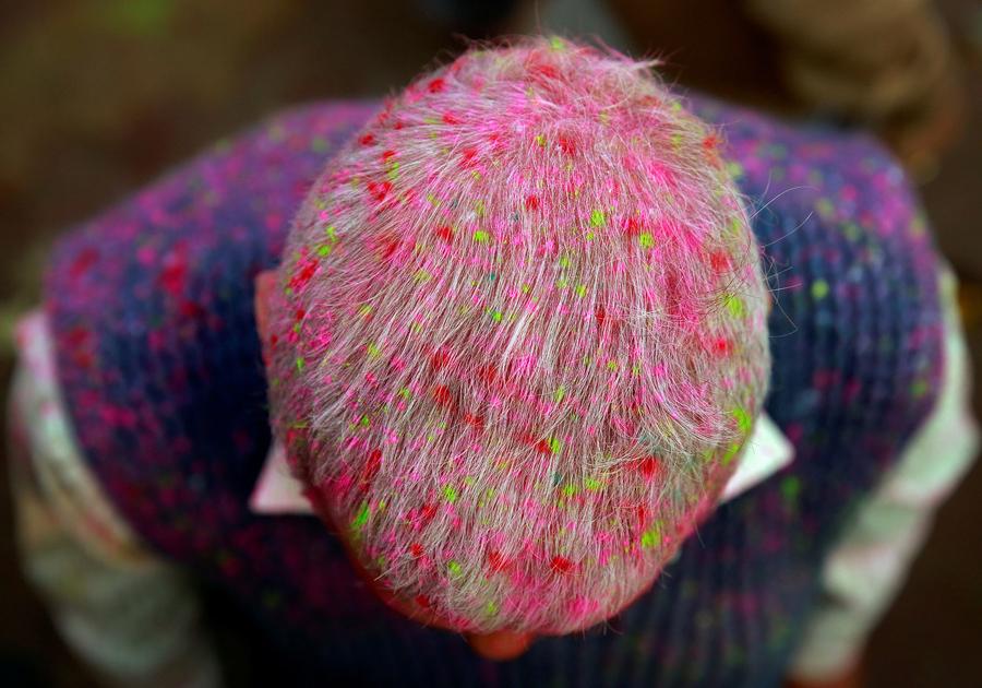 Голова мужчины покрыта цветным порошком, он стоит у храма в Вриндаване, Индия.