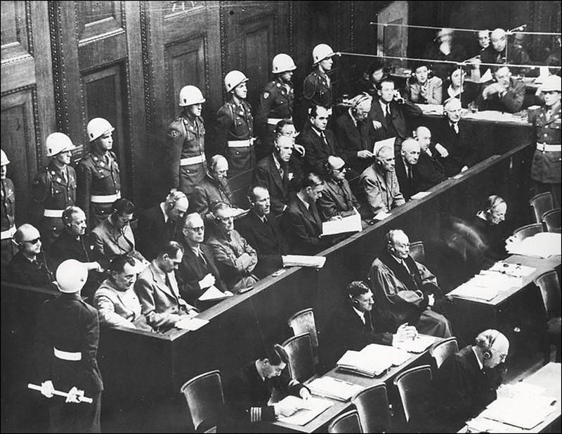 (1-й ряд (слева направо): Геринг, Гесс, Риббентроп, Кейтель, Кальтенбруннер, Розенберг, Франк, Фрик, Функ, Шахт; 2-й ряд: Дениц, Редер, Ширах, Заукель, Иодль, Папен, Зейсс-Инкварт, Шпеер, Нейрат, Фриче. Согласно вердикту суда 1 октября 1946 года Геринг, Риббентроп, Кейтель, Розенберг, Кальтенбруннер, Фрик, Франк, Штрейхер, Заукель, Иодль, Зейсс-Инкварт и заочно Борман приговорены к смертной казни через повешение; Гесс, Функ и Редер – к пожизненному заключению в тюрьме Шпандау; Ширах, Шпеер – к 20 годам; фон Нейрат – на 15 лет; Дениц – на 10 лет)