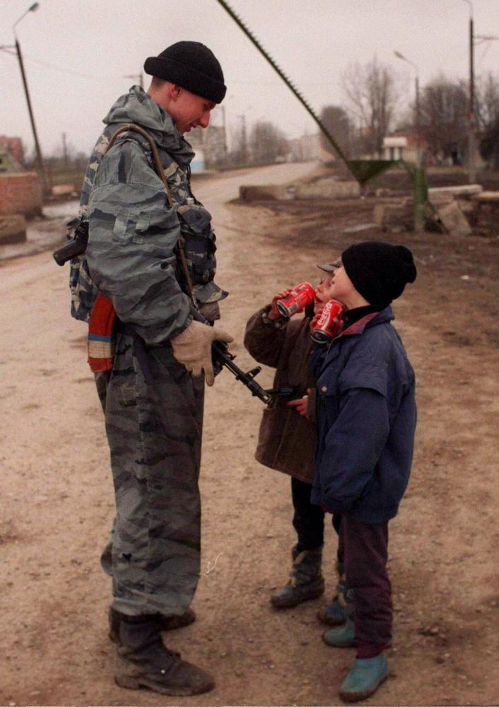 Солдат разговаривает с детьми неподалеку от Грозного, март 1996 года.