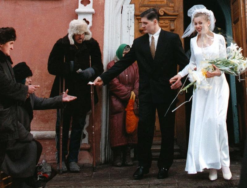 Молодожены подают нищим, покидая церковь в Красноярске, октябрь 1998 года.