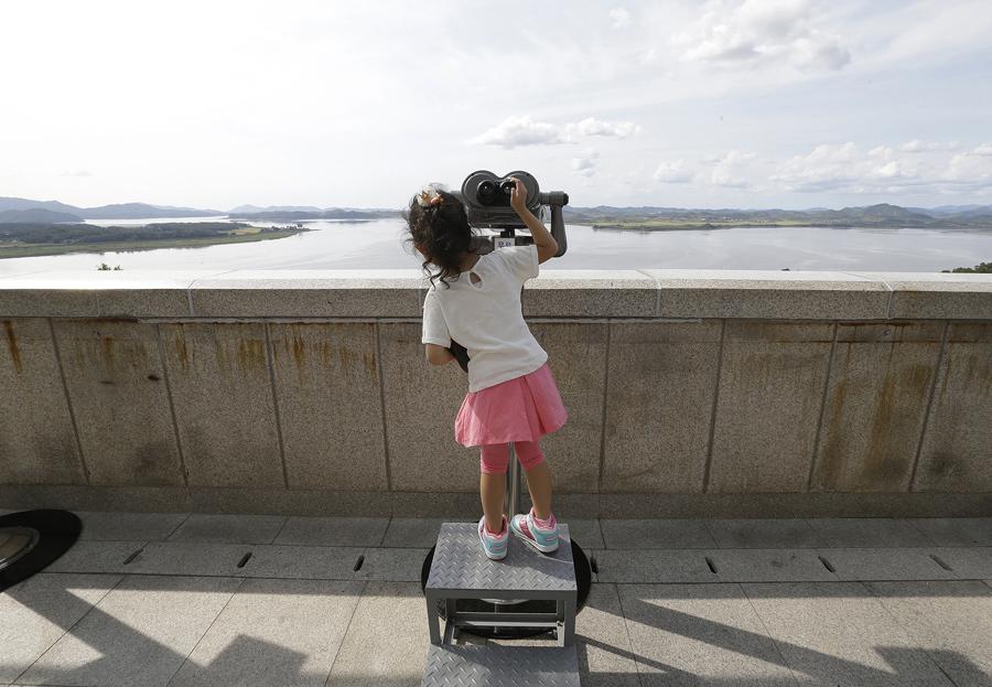 Южнокорейская девочка рассматривает северокорейскую территорию, 13 сентября 2016 года.