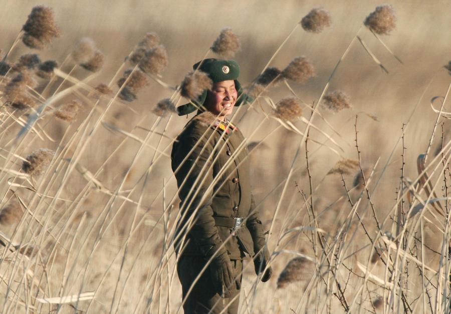 Северокорейский солдат улыбается возле города Синыйджу, сфотографировано с противоположной китайской границы города Даньдун, 6 января 2016 года.