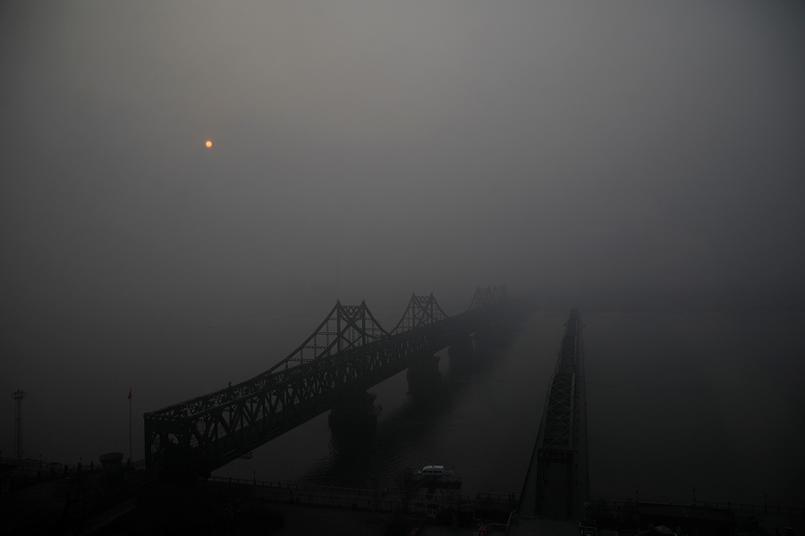 Солнце поднимается сквозь туман над разбитым мостом через реку Ялу , соединяющими Северную Корею и Китай, 30 марта 2017.
