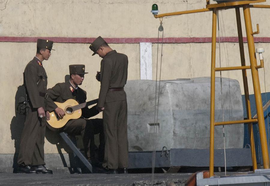 Северокорейский солдат играет на гитаре на берегах реки Ялу, 15 апреля 2009 года.
