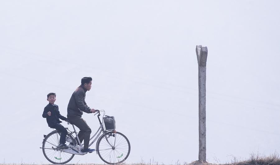 Северокорейский человек едет с ребенком на велосипеде возле Синыйджу, напротив китайского города Даньдун, 15 апреля, 2017.