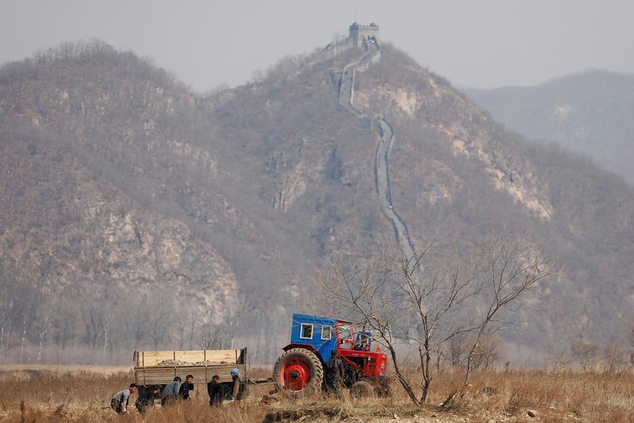 Северокорейские фермеры работают в поле, видна часть Великой стены на китайской стороне реки Ял, к северу от города Синыйджу в Северной Корее, 2 апреля, 2017.