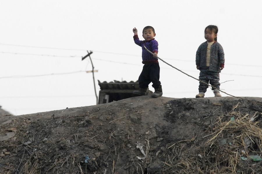Северокорейские дети реагируют на фотографа на берегу реки Ялу близ северокорейского города Синыйджу, 16 декабря 2006 год.