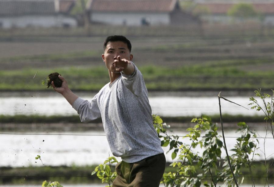 Северокорейский солдат бросает землей в фотографа на берегу реки Ялу, 27 мая 2010 года.