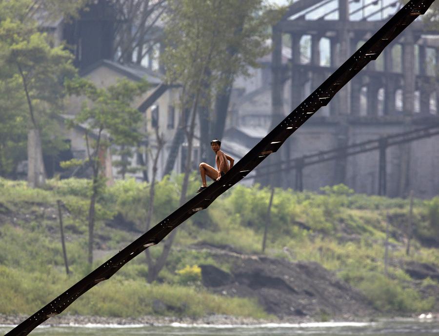 Мужчина спускается по лестнице заброшенной фабрики вдоль берега реки Ялу близ северокорейского города Кинг Чэн, 12 сентября 2008 года.