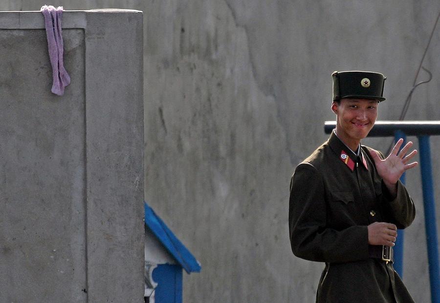 Северокорейский пограничник улыбается фотографу, 9 октября 2006 года.