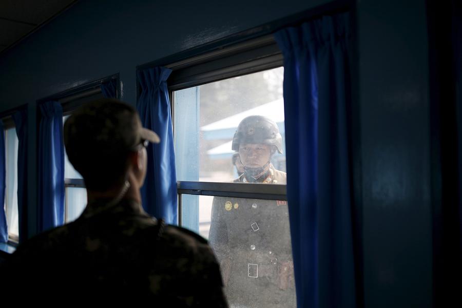Север (справа) и южнокорейские солдаты смотрят друг на друга через окно конференц - зала в Организации Объединенных Наций , Южная Корея, 30 марта 2016 года.