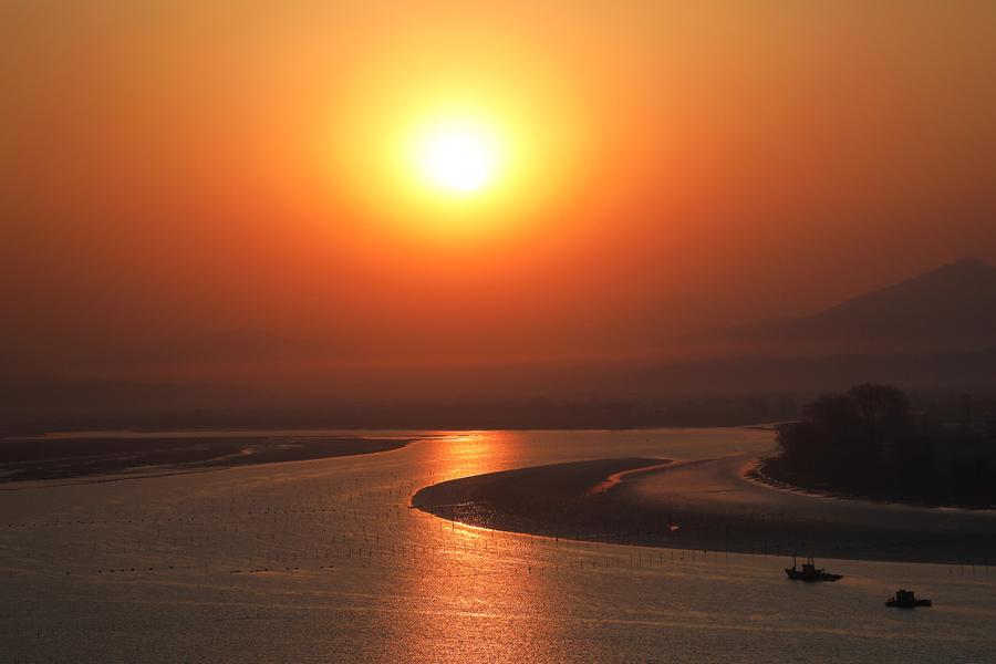 Солнце поднимается с северокорейской стороны реки Ялу недалеко от города Синыйджу, вид из Даньдуна, Китай, 1 апреля, 2017.