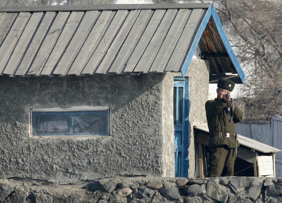 Северокорейский пограничник направляет свое оружие в сторону фотографа на берегу реки Ялу близ северокорейского города Хесане, 1 декабря 2008 года.