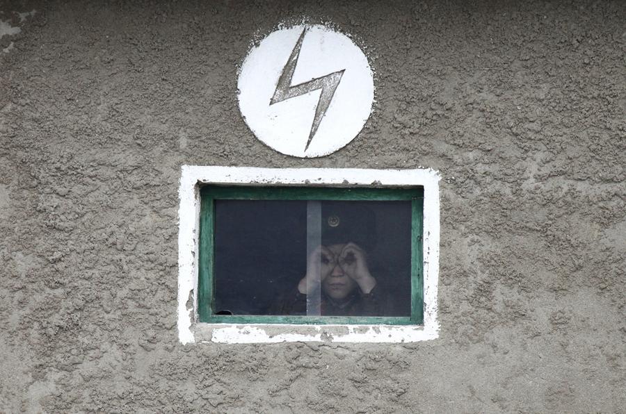Северокорейский солдат смотрит из окна сторожевой башни, на берегу реки Ялу, около 100 километров от северокорейского города Синыйджу, напротив китайского пограничного городского округа Даньдун, 16 апреля 2013 г.