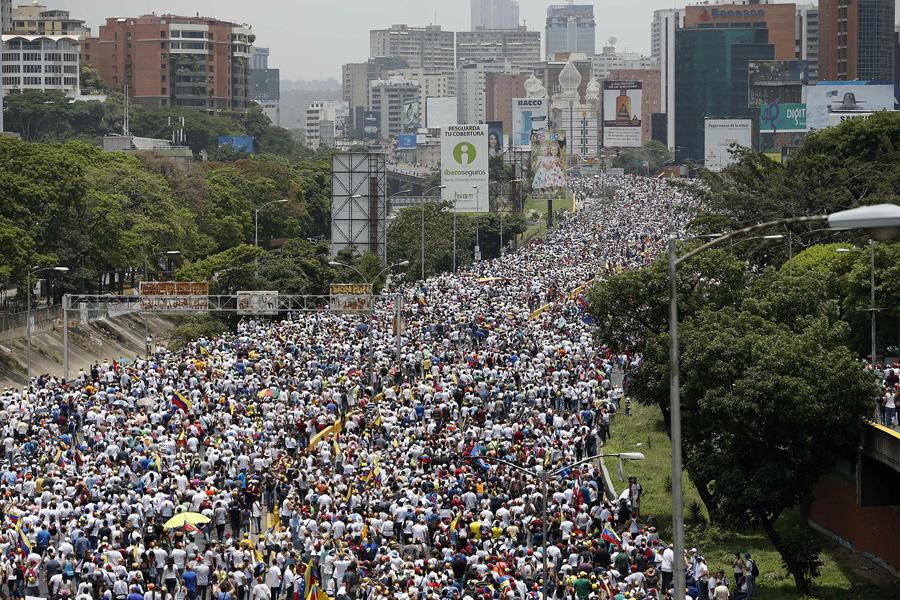 Тысячи антиправительственных демонстрантов маршеруют по шоссе в Каракасе, Венесуэла, 19 апреля 2017. Противники президента Николаса Мадуро призвали венесуэльцев выйти на улицы, чтобы выступить против лидера социалистов.