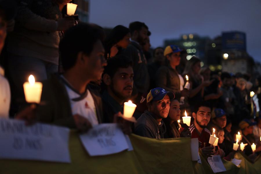 Протестующие держат свечи во время бдения в Буэнос - Айресе, Аргентина, 19 апреля 2017. Противники президента Мадуро живущие в Аргентине собрались на площади в аргентинской столице, чтобы поддержать демонстрантов в Венесуэле.