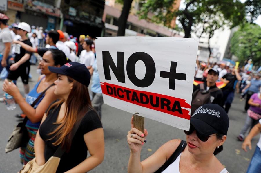 Демонстранты с транспарантами с надписями «Нет больше диктатуры» против президента Венесуэлы в Каракасе, 19 апреля 2017.