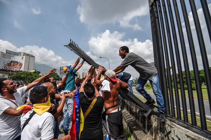 Демонстранты пытаются снести забор на авиабазе Ла Карлота во время митинга против президента Венесуэлы Мадуро, Каракас, 19 апреля, 2017.