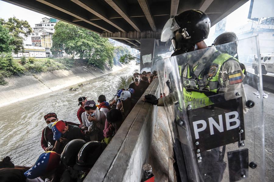 Полиция следит за демонстрантами после столкновений во время митинга против президента Венесуэлы Николаса Мадуро, Каракас, 19 апреля, 2017.