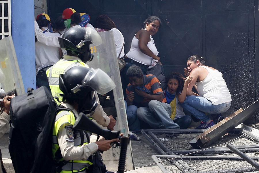 Антиправительственные демонстранты укрываться от полиции во время протестов в Каракасе 19 апреля 2017 года.