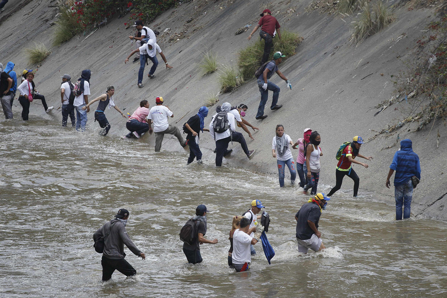 Люди идут вброд через реку Рио-Гуайра, они убегают от сил безопасности во время антиправительственных протестов в Каракасе 19 апреля 2017.