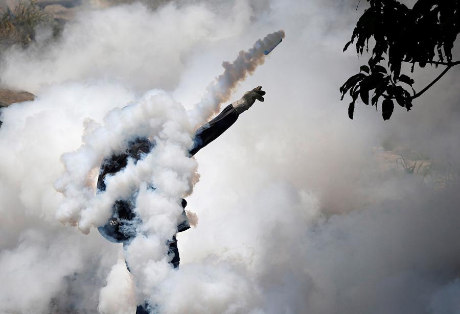 Демонстратор откидывает гранату со слезоточивым газом во время столкновения с полицией в Каракасе 19 апреля 2017 г.