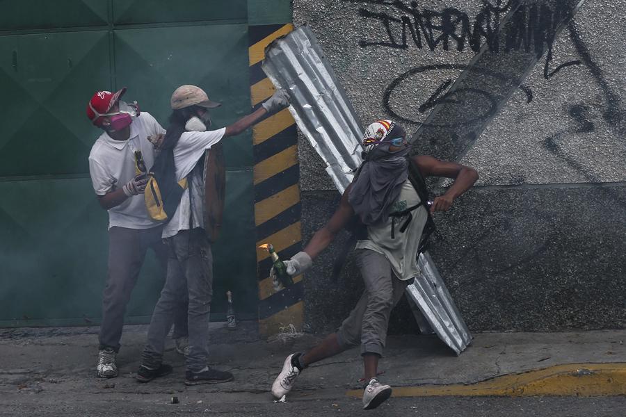 Мужчина бросает коктейль Молотова в полицию, Каракас 19 апреля 2017 года.