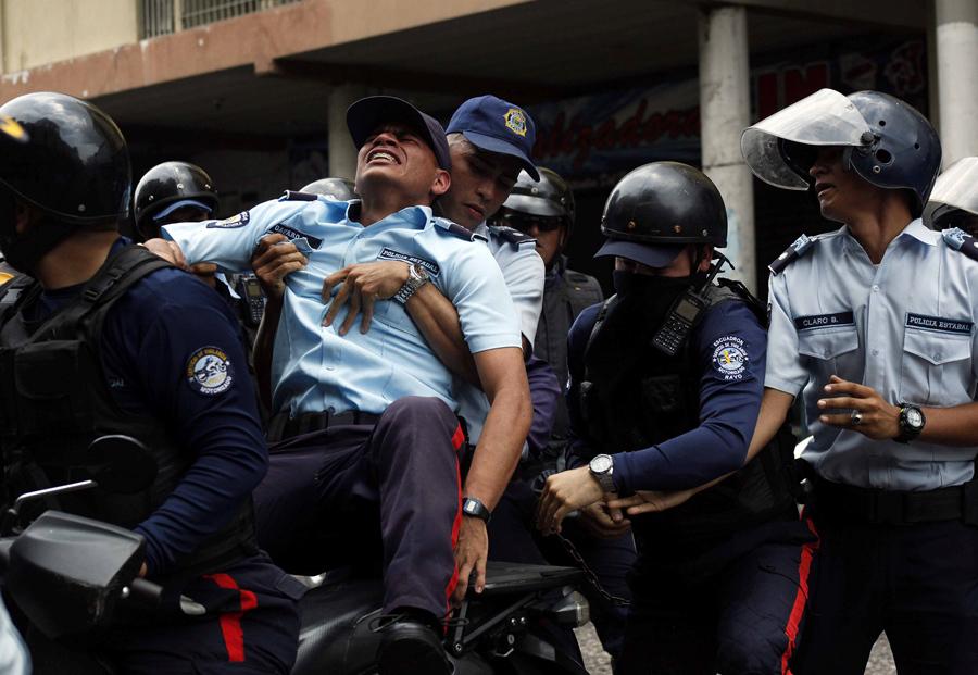 Полиция помогает травмированному коллеге во время столкновений с сторонниками оппозиции в Сан-Кристобале, Венесуэла, 19 апреля, 2017.