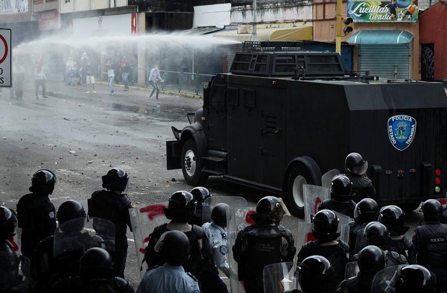 Сторонники оппозиции в столкновении с полицией во время акций протеста против президента Мадуро в городе Сан-Кристобаль, запад Венесуэлы, 19 апреля, 2017.