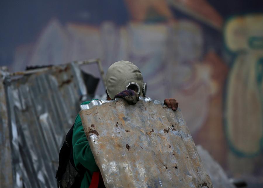 Оппозиционер укрывается металлическим листом во время столкновения с полицией в Каракасе 19 апреля 2017.