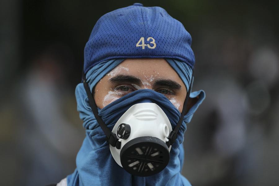 Антиправительственный протестующий в маске во время столкновений с силами безопасности в Каракасе 19 апреля 2017.