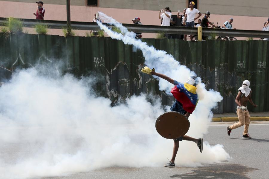Протестующий откидывает гранату со слезоточивым газом во время антиправительственных протестов в Каракасе 19 апреля 2017.