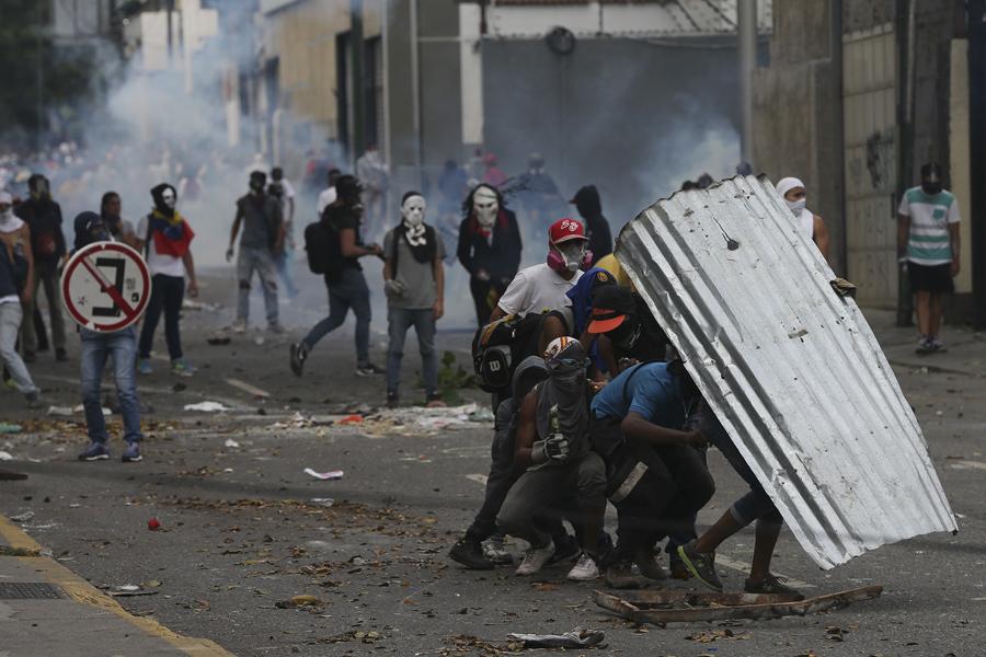 Демонстранты укрываются куском гофрированной кровли во время антиправительственных протестов в Каракасе 19 апреля 2017.