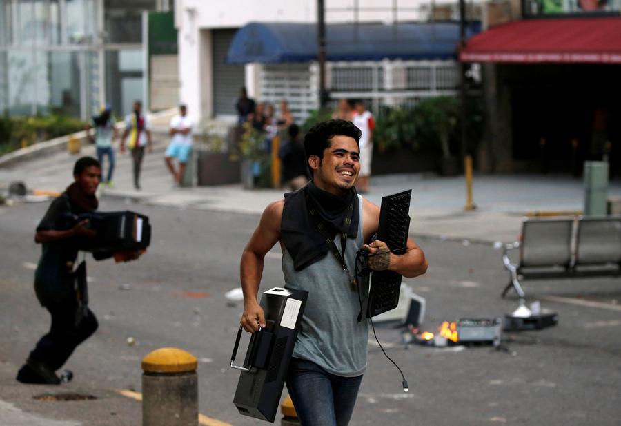 Люди бегут с награбленной техникой из офисного здания во время так называемой «матери всех маршей» в Каракасе 19 апреля 2017 года.