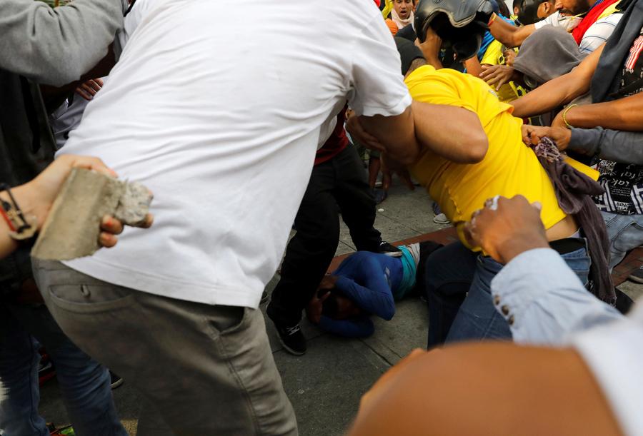 Демонстранты бьют человека, которого они обвинили в воровстве (на земле), Каракас, 19 апреля 2017.