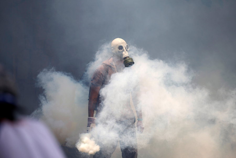 Протестующий держит баллончик со слезоточивым газом во время столкновений с полицией в Каракасе, Венесуэла, 19 апреля, 2017.