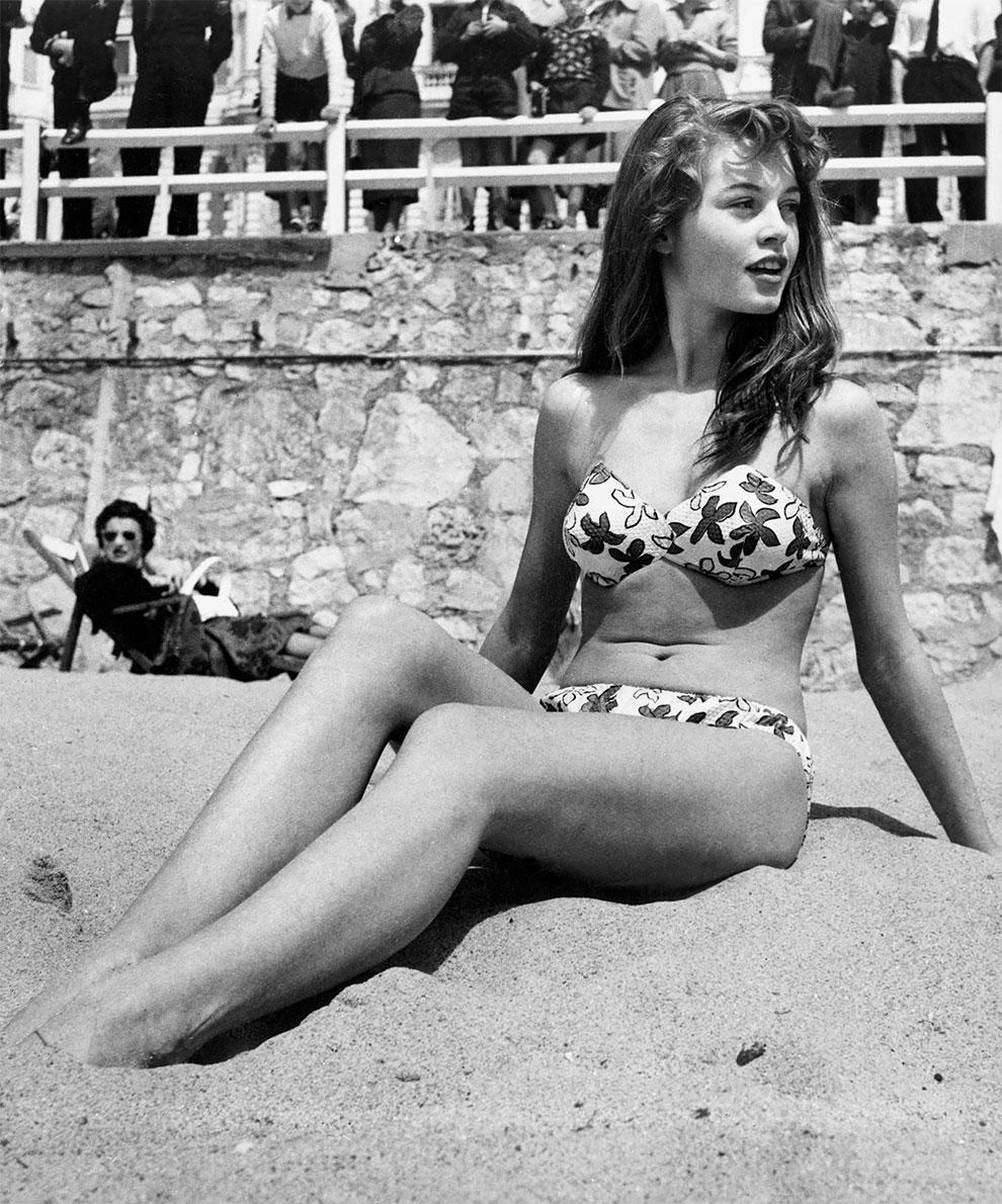Французская актриса Брижит Бардо, сидя на пляже во время Каннского кинофестиваля, 1953г.