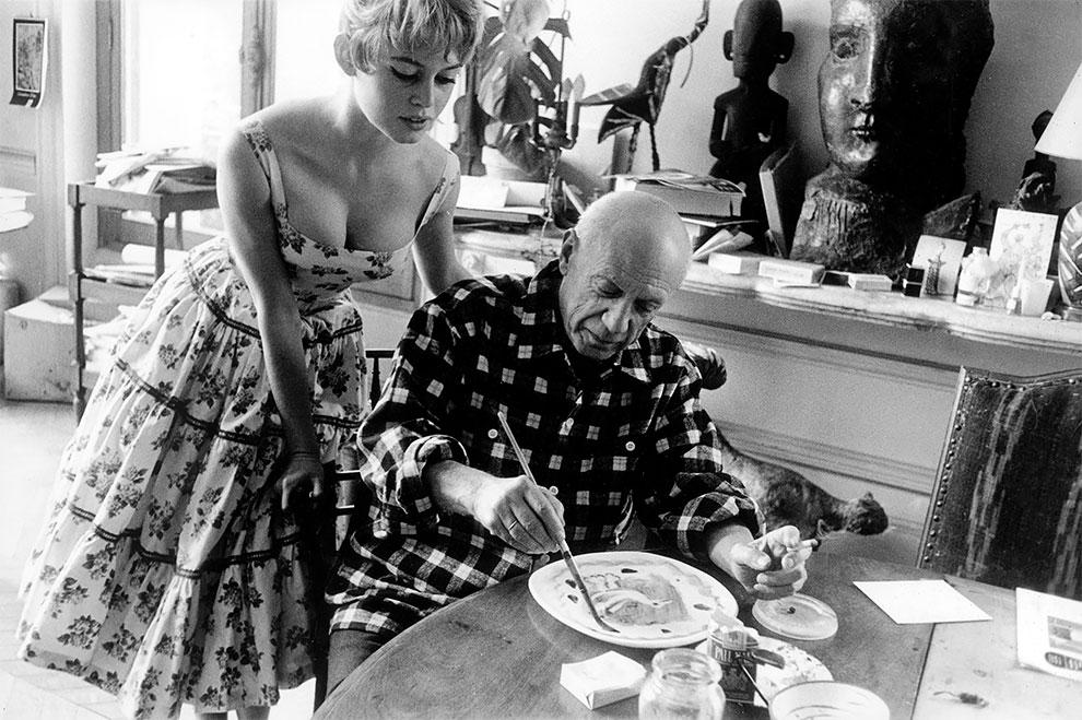 Актриса Брижит Бардо смотрит как работает Пабло Пикассо в своей студии в Валлорисе в рамках Международного кинофестиваля в Каннах 1956 год.