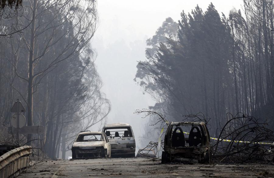 Сгоревшие автомобили перекрыли дорогу между Castanheira de Pera и Figueiro dos Vinhos, центральная Португалия, 18 июня 2017.