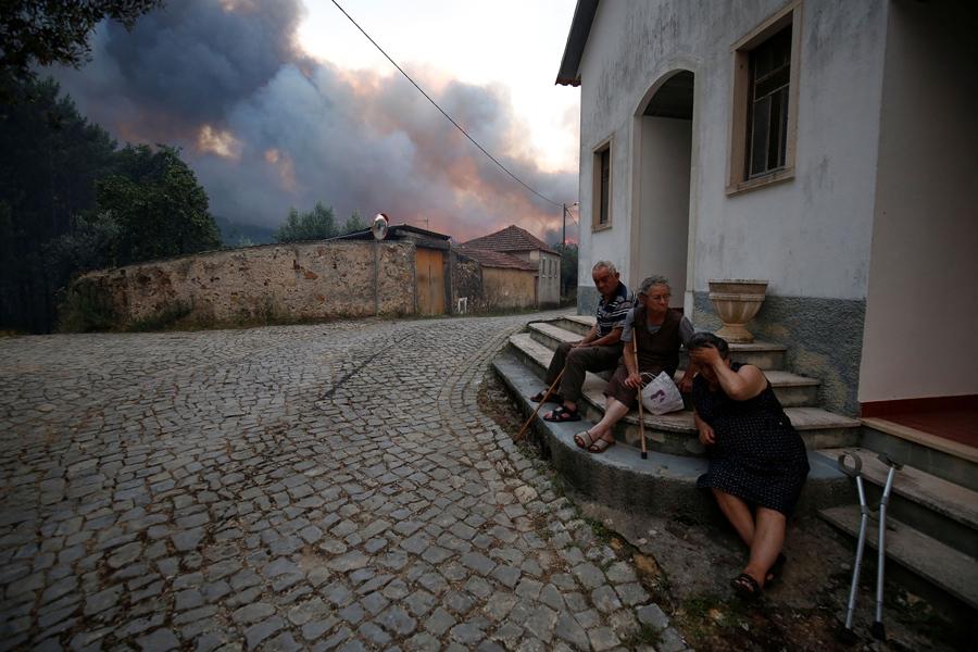 Сельчане сидят на улице во время лесного пожара возле села Fato, центральной Португалии, 18 июня, 2017.
