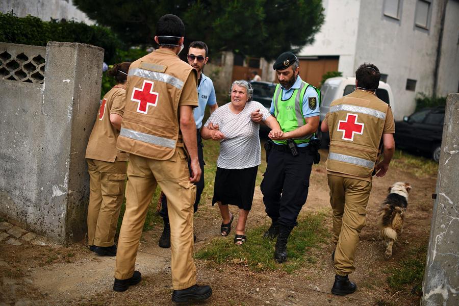 Красный Крест и сотрудники полиции эвакуируют людей из домов, 18 июня 2017 года.
