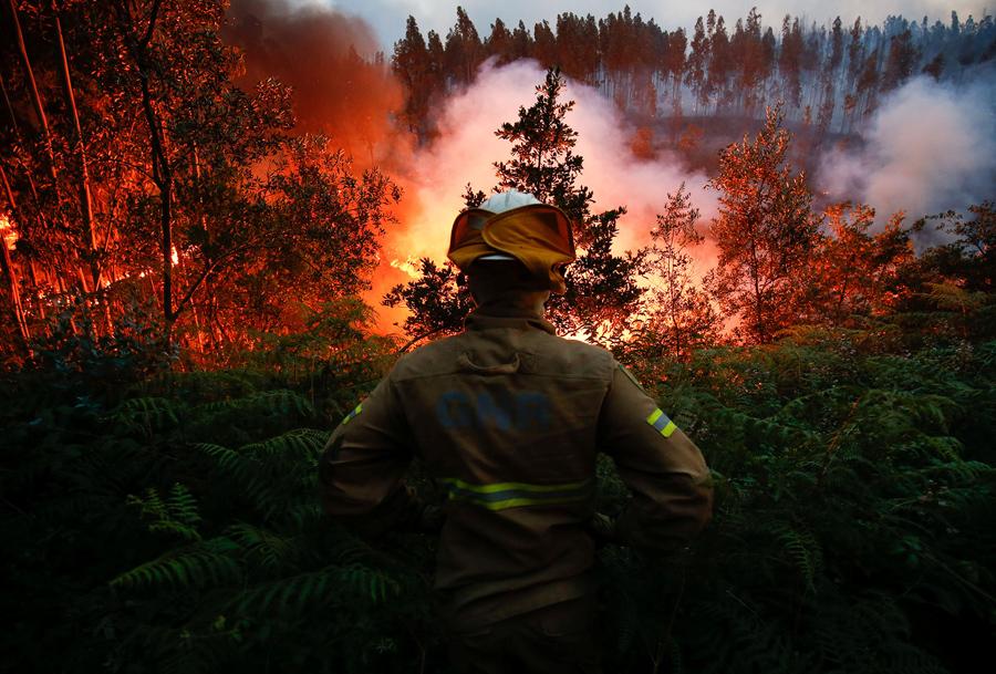 Пожарный наблюдает за лесной пожар около села Fato, Португалия, 18 июня, 2017.