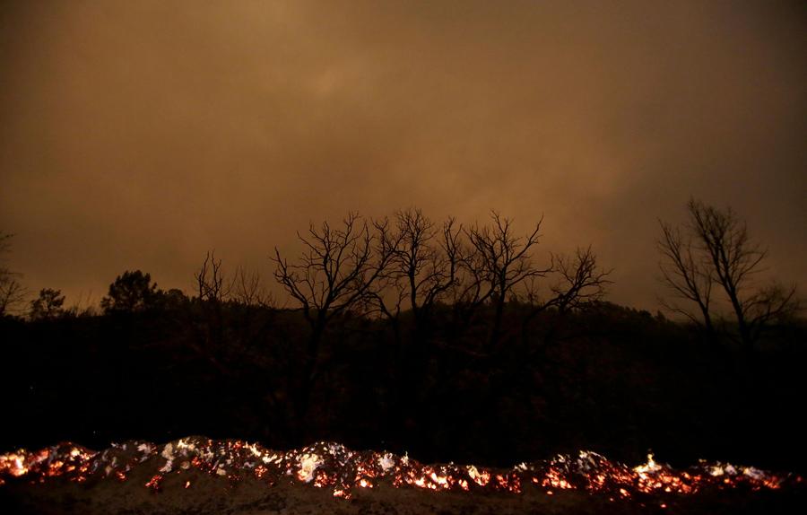 Огонь и дым во время лесного пожара в Albares, в центральной Португалии, 18 июня, 2017.