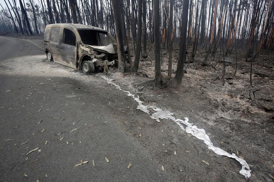 Сожженный фургон и деревья, после лесного пожара за пределами Pedrogao Grande, Португалия, 19 июня, 2017.
