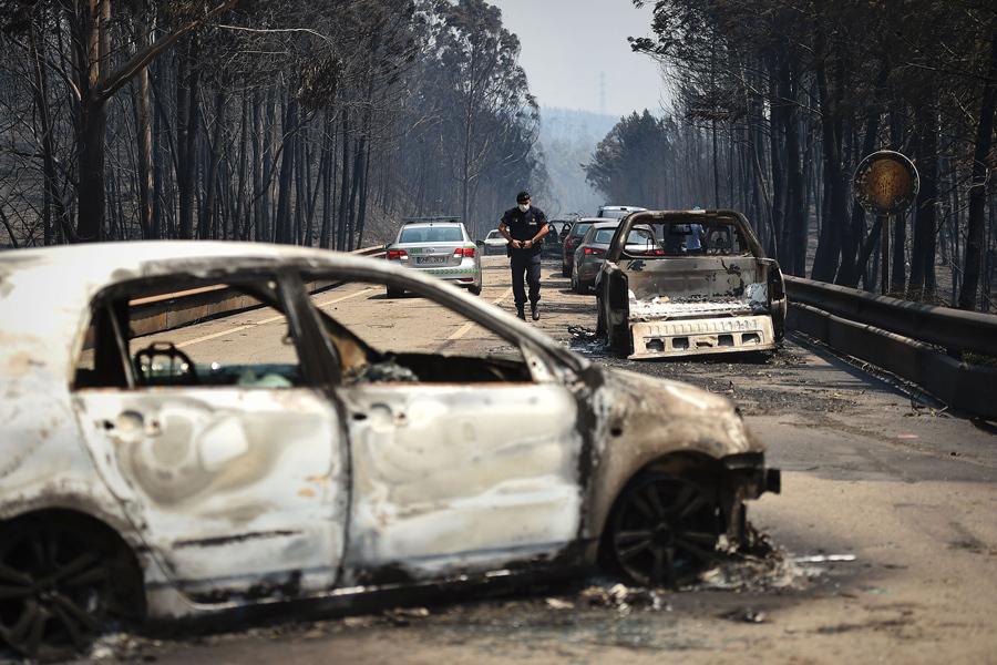 Полицейский ходит по дороге мимо сгоревших автомобилей после лесного пожара в Figueiro dos Vinhos, 18 июня 2017.