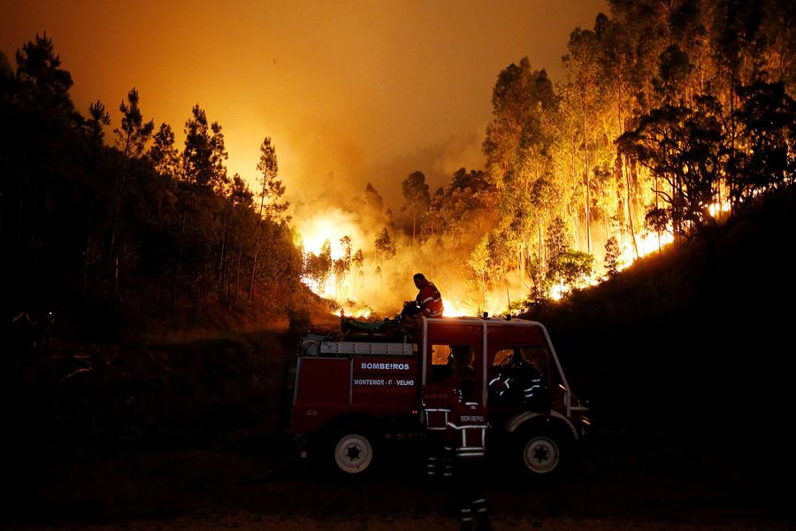 Пожарные работают, чтобы потушить лесной пожар возле Bouca, в центральной Португалии, 18 июня, 2017.