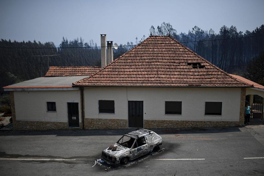 Сожженный автомобиль перед домом, после пожара в Figueiro dos Vinhos.