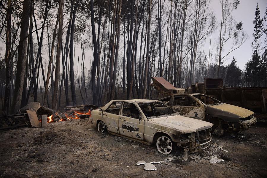 Сожженные машины и опустошенный лес недалеко от Castanheira de Pera, Португалия.