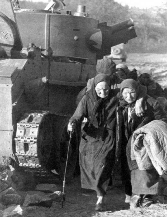 Советские беженцы проходят у сгоревшего фашистского танка. Июнь 1941.